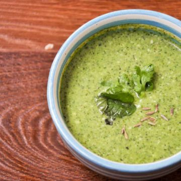 Green chutney served in blue bowl.