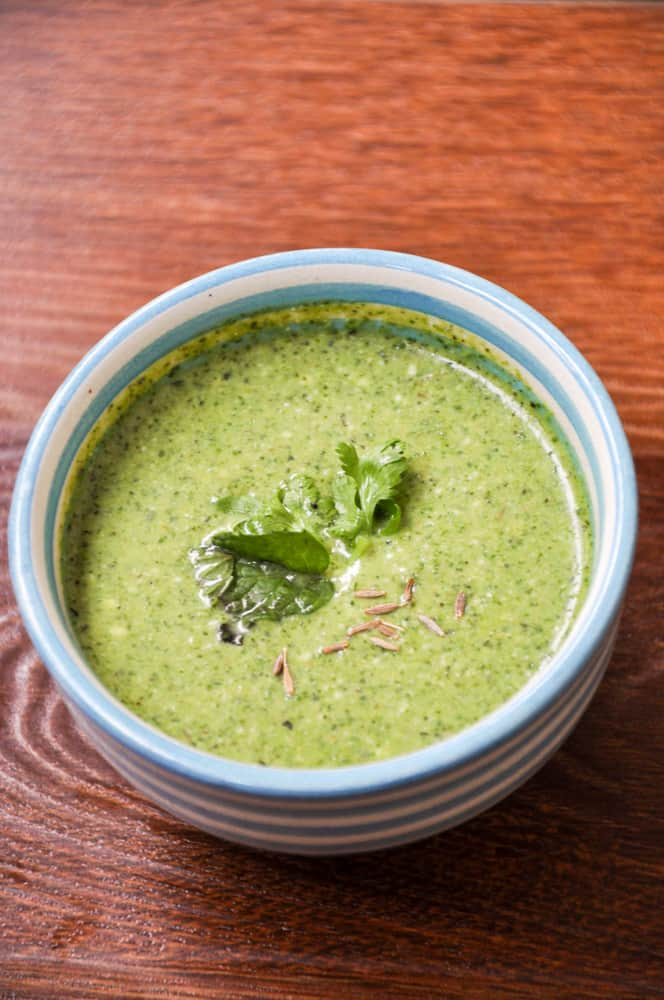 Green Chutney served in small chutney bowl with mont leaves and cumin garnish.