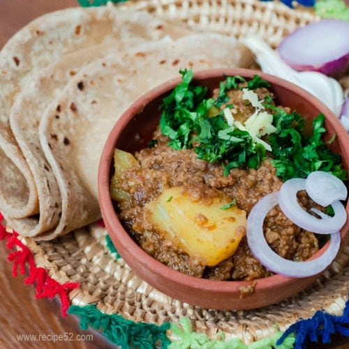 Keema aloo served with roti and onion slices over a colorful Sindhi plate.