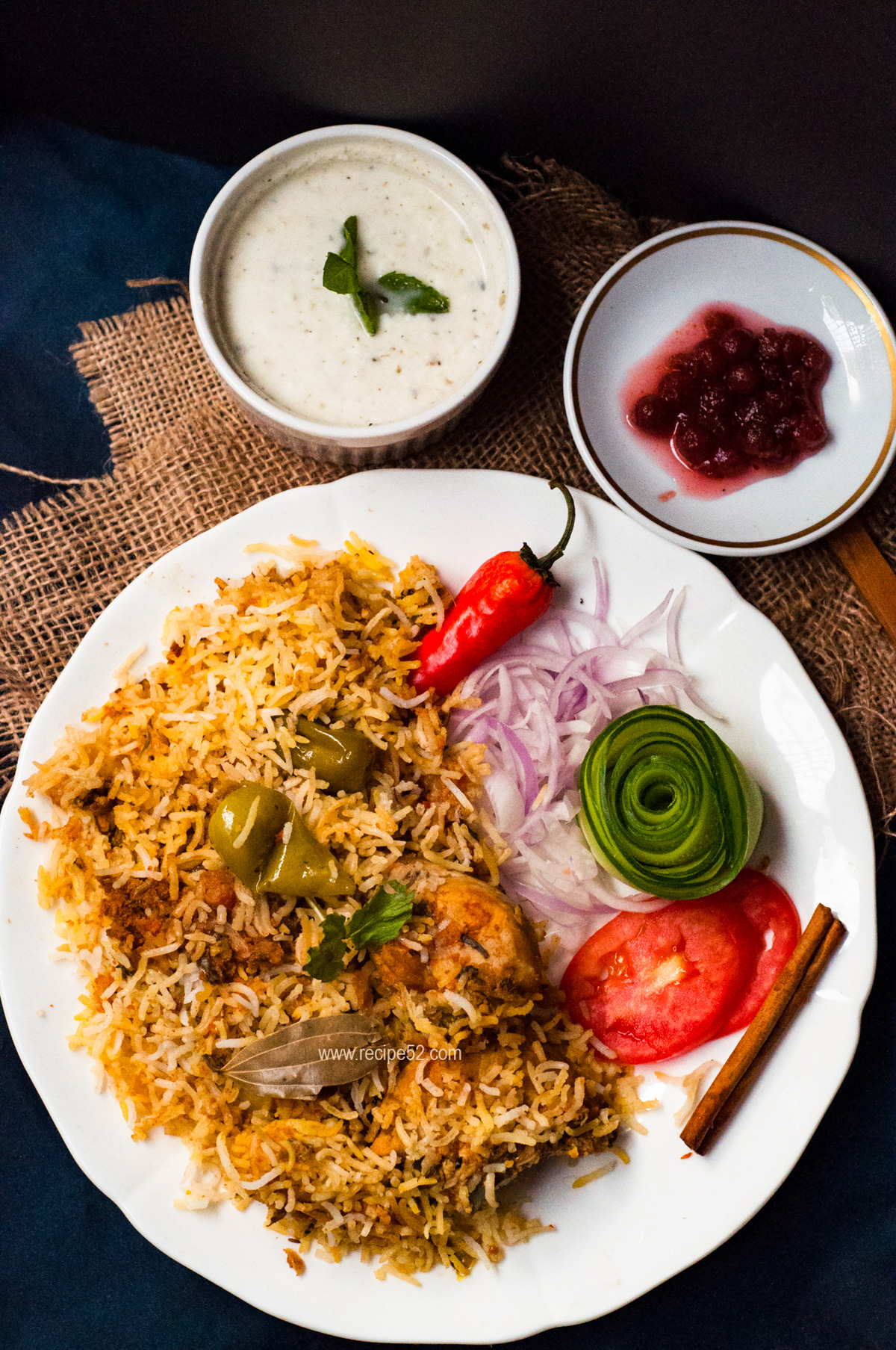 Pakistani Chicken biryani served in a plate with condiments on the side.
