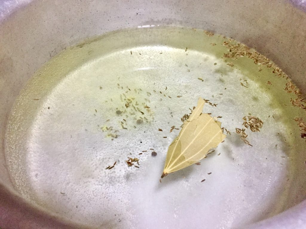 Boil water with spices for chicken biryani.