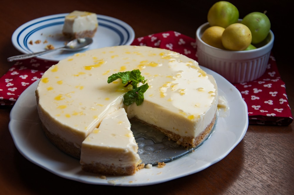 Lemon cheesecake with lemons in the background.