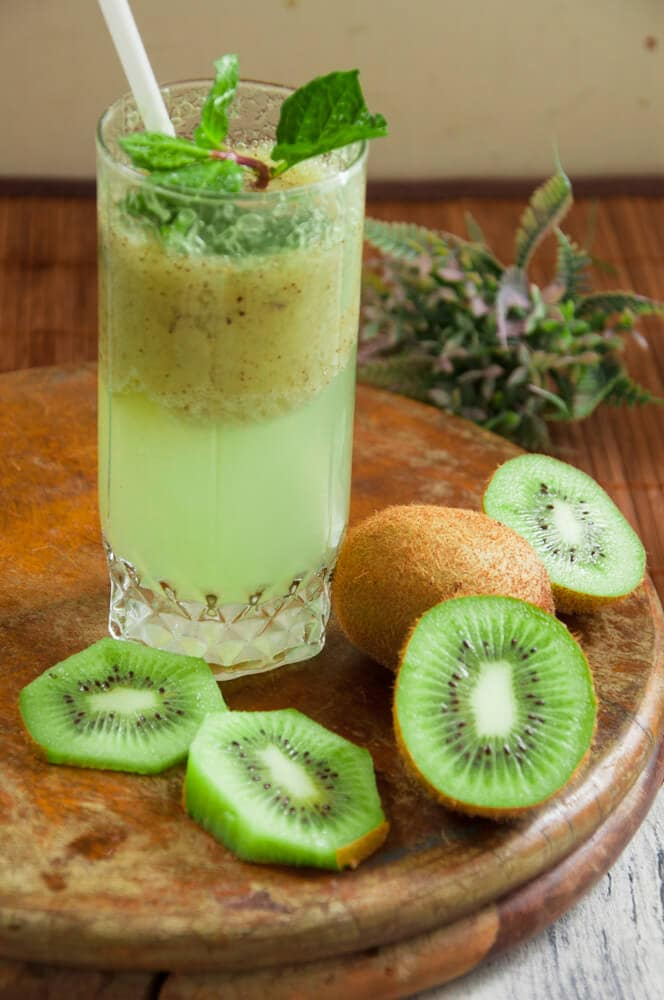 Kiwi Drink served in a glass with straw and mint leaves.