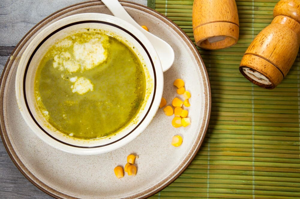 spinach soup with chicken broth and sweet corns served in a bowl.