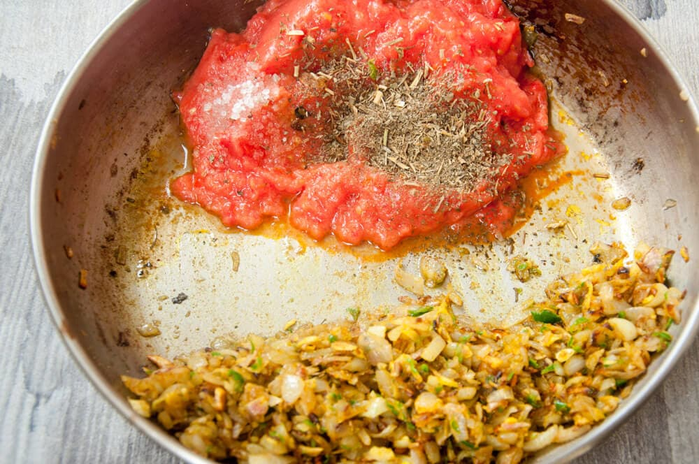Add tomatoes to the onion mixture.