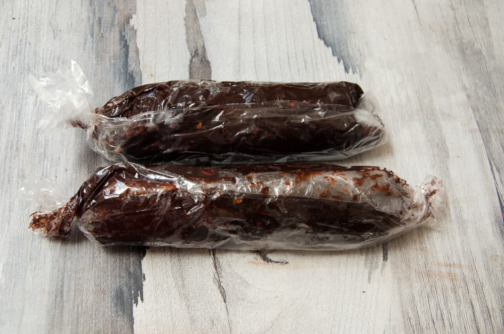 Roll chocolate salami mixture into platic sheets and roll into two logs.