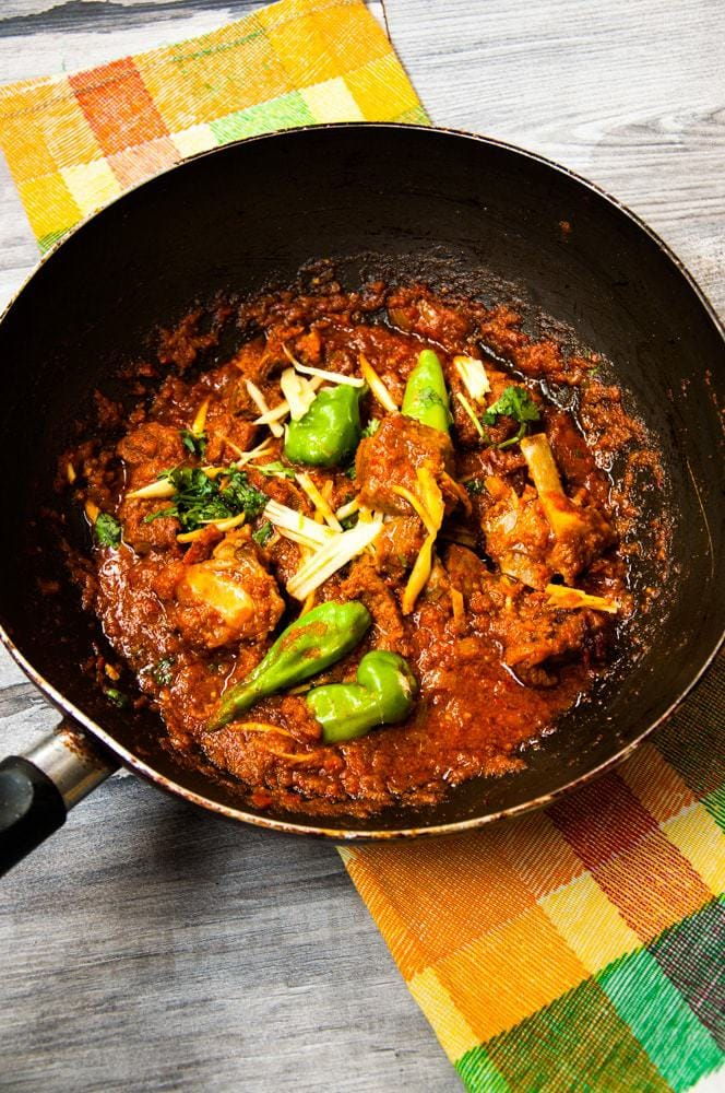 Lamb Karahi kept on colourful spread with chili and ginger garnish.
