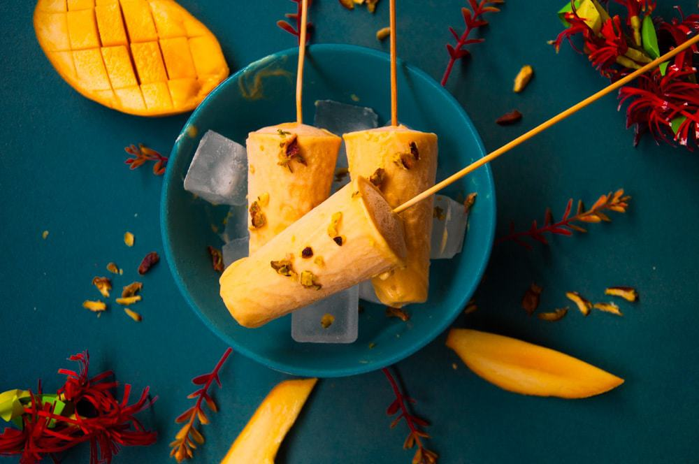 Mango kulfi in a bowl over ice cubes with mango slice on a side.