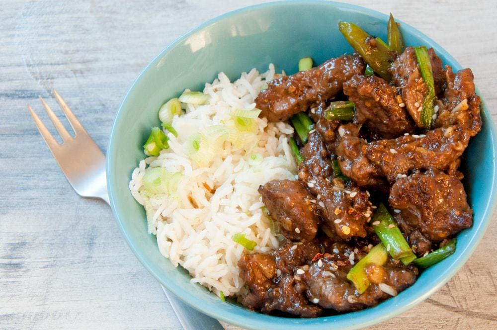 Mongolian beef served with rice in a bowl.