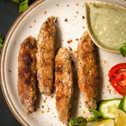 Seekh kebab served on a plate with chutney and salads on the side.