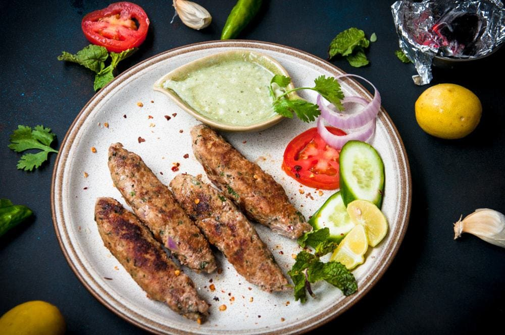 Brown plate on a black background with Pakistani seekh kabab and salad on it.