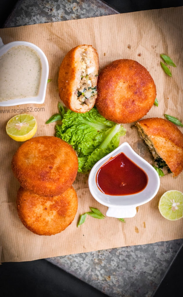 Four aloo keema patties or cutlets on a brown paper with chutney and ketchup, lemon wedges and salad leaf on the side.