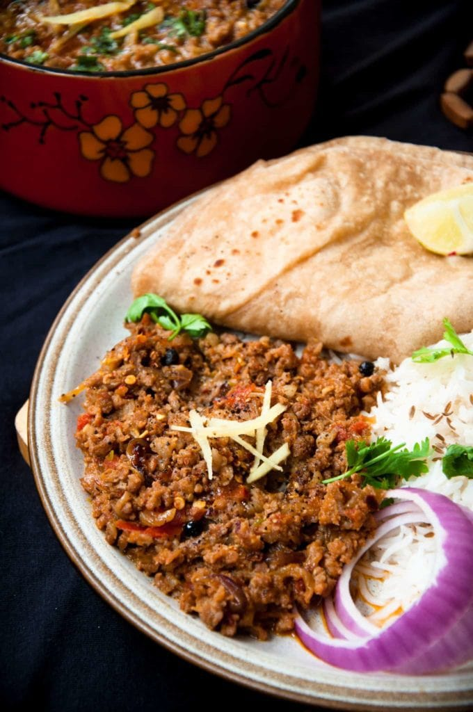 Keema served in a plate with onion slices, roti and rice. Ginger is used to garnish.