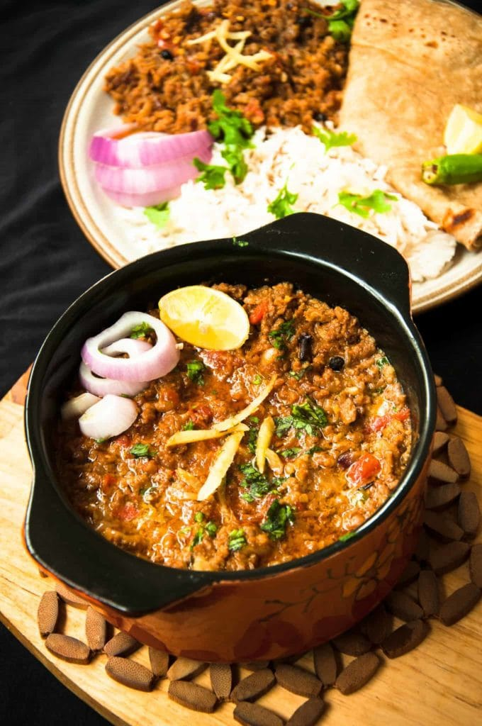 Keema serves in a bowl with roti and rice in the background.