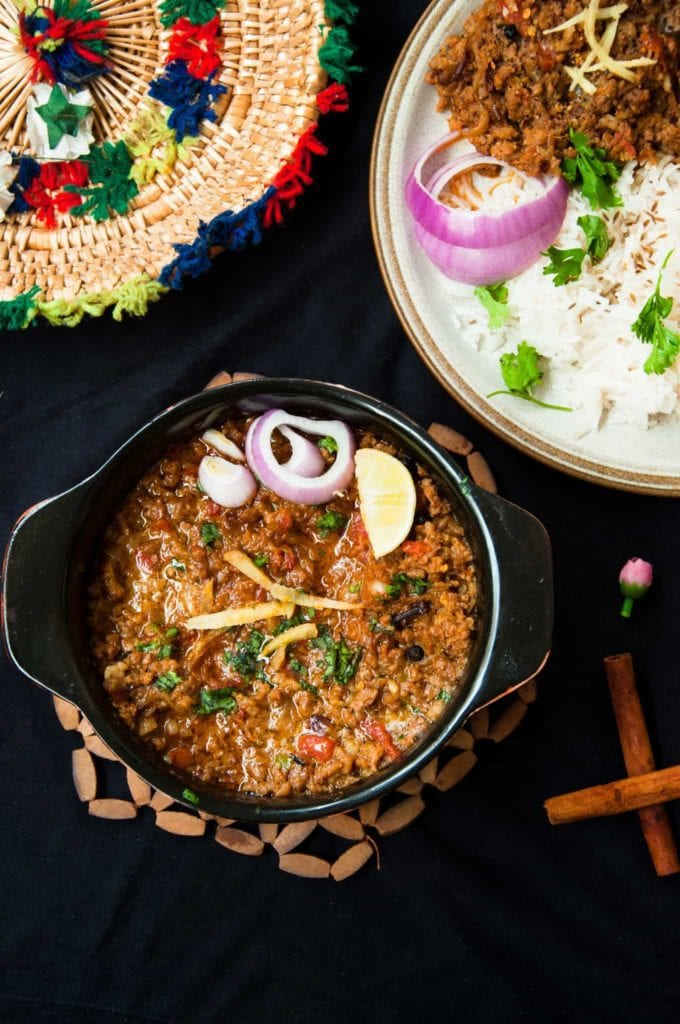Keema served in small black pot with onion slices and lemon wedges on the side.