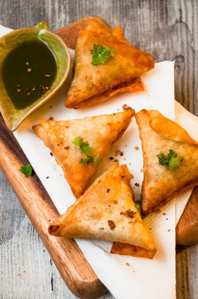 Four Samosa Triangles served in a wooden tray with green sauce on the side.