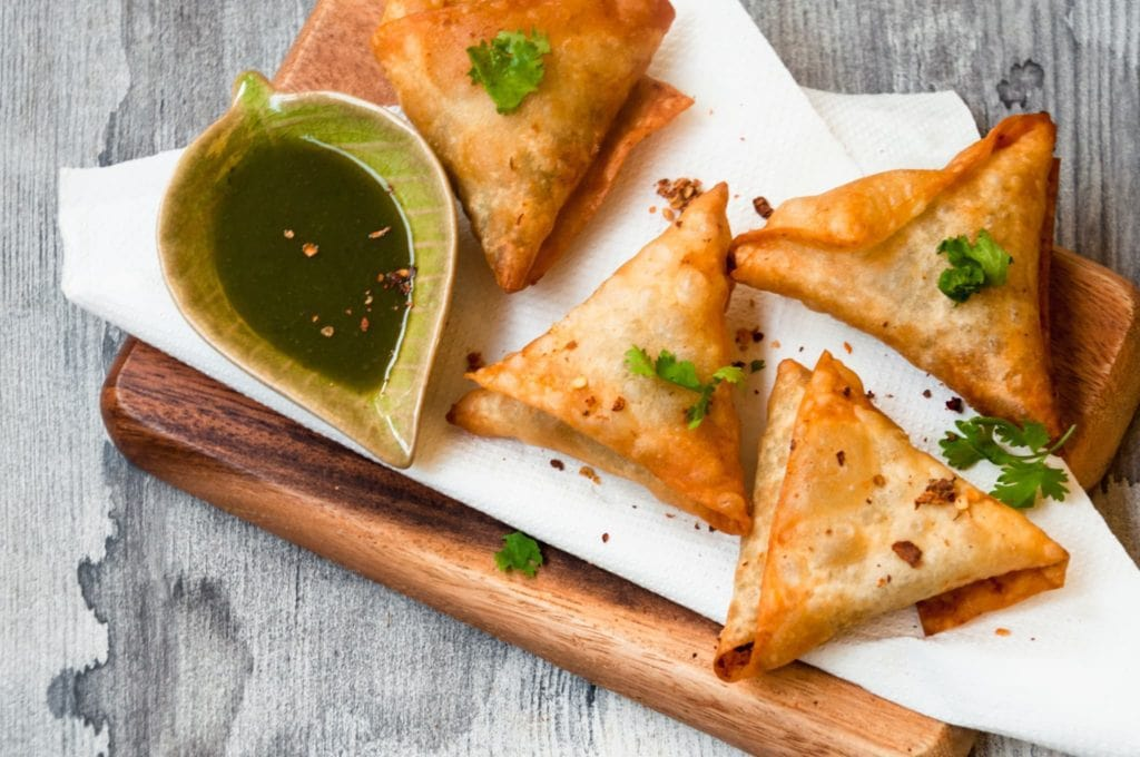 Fried Beef samosa served on tissue with cilantro leaves garnish.