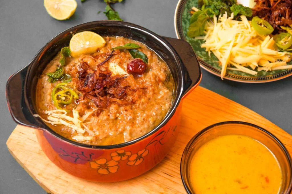 Haleem served with lemon wedges, kadhi, ginger, mint and fried onions.