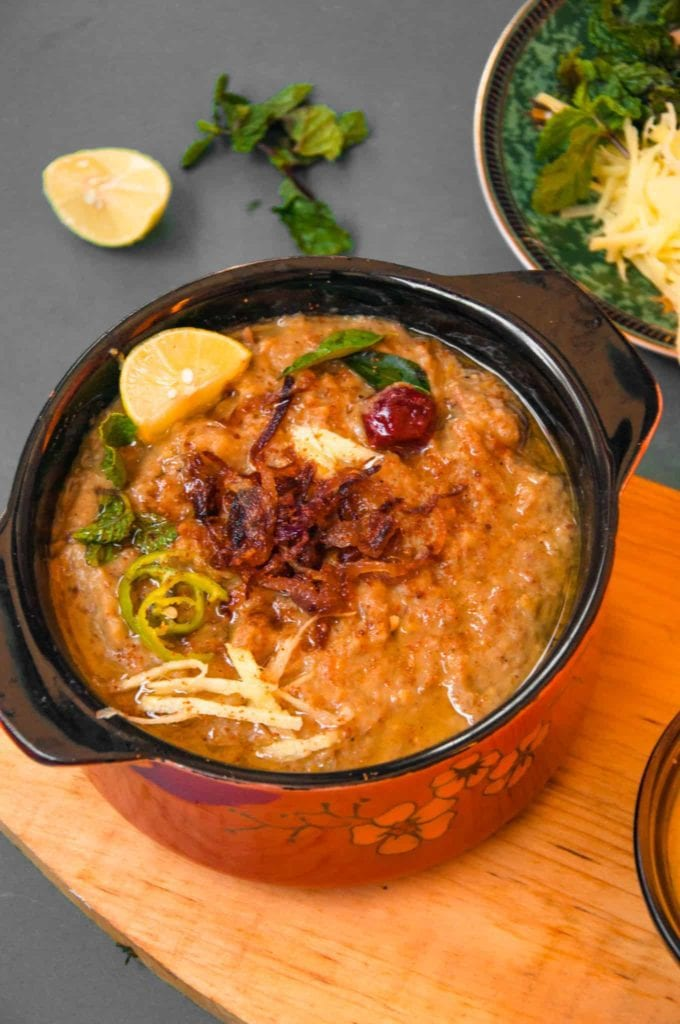 Haleem served in a pot with condiments in the background.