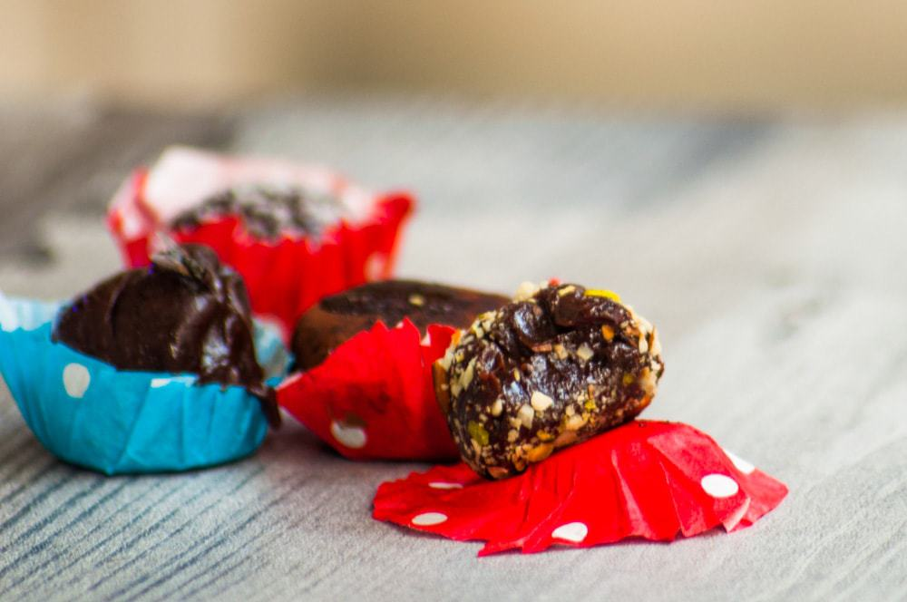 A half chocolate condensed truffles resting on the red bon bon cup, teeth marks are visible.