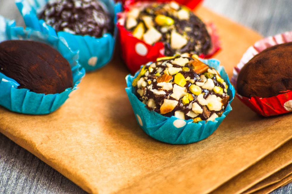 Brigadeiro truffles with pistachio, cocoa and coconut variation served in red and blue dotted bonbon cups.