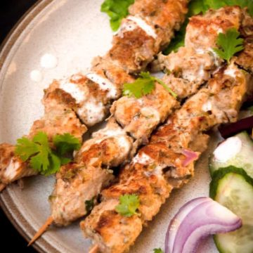 Chicken malai tikka with cream drizzled over it.