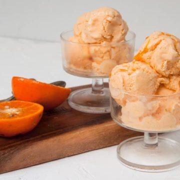 2 orange ice cream cups with fresh orange on the side.